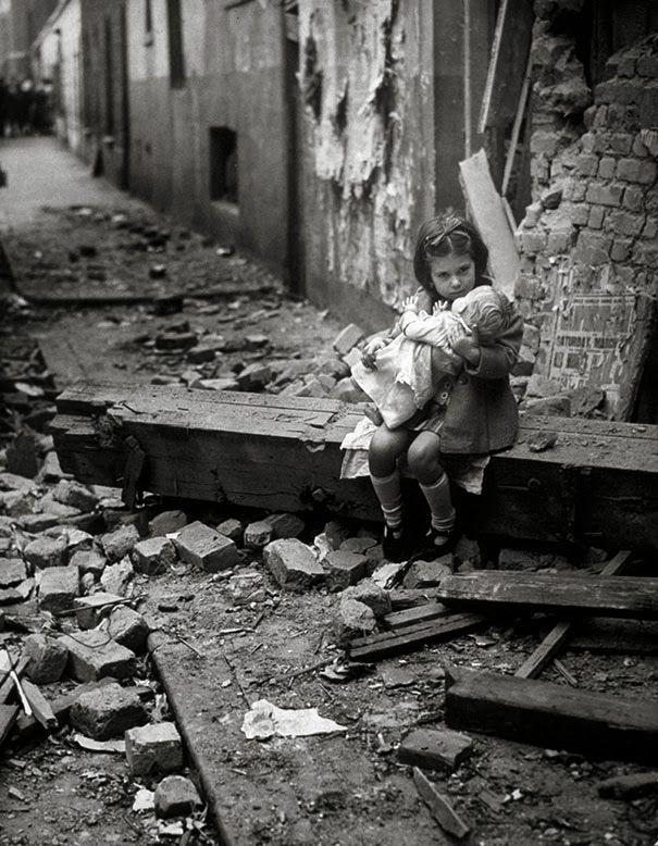 Una bambina con la sua bambola siede sulle macerie della propria casa bombardata, Londra, 1940.