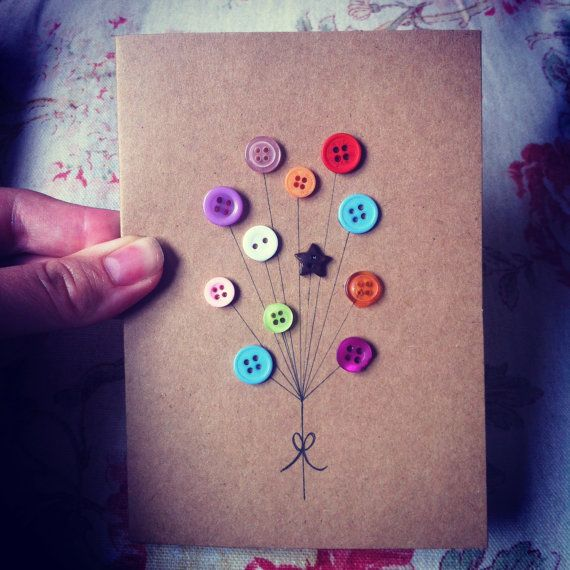 A handmade greeting card made from recycled Kraft featuring a mix of wood, coconut-shell and colourful buttons to make a balloon bouquet. Very