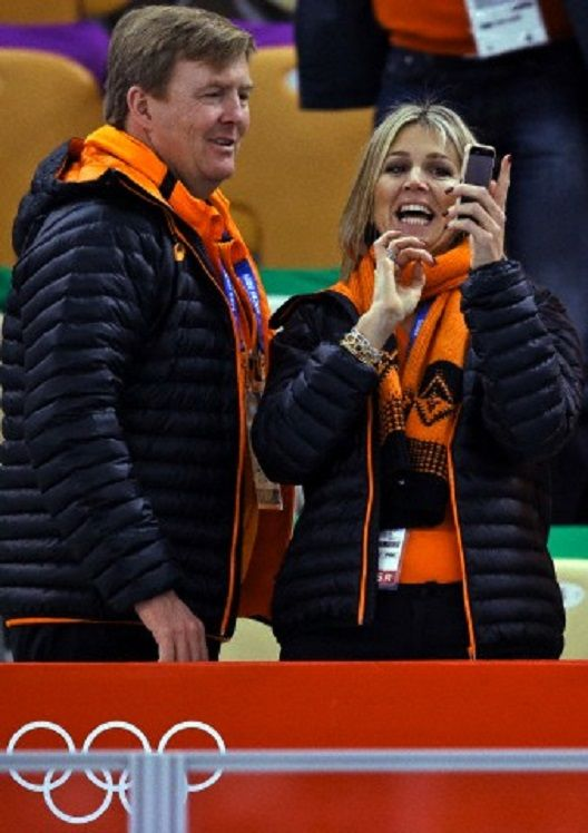 Dutch King Wilem-Alexander, left, looks at the phone of Queen Maxima during the women's 3,000-meter speedskating race at the Adler Arena Skating Center during the 2014 Winter Olympics, 09.02.2014, in Sochi, Russia.