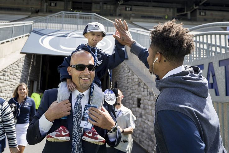 Penn State head coach James Franklin carries Josiah Viera as he greets safety Marcus Allen before the Pitt game