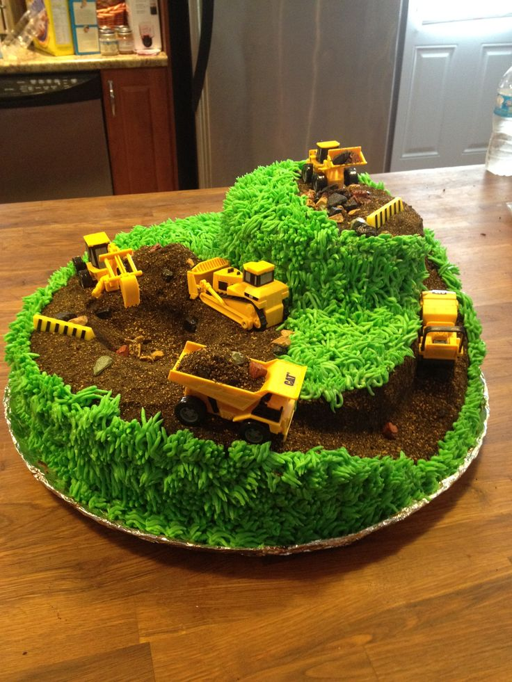 """Construction cake with """"risers"""" and holes dug into the surface of it. The only downside is that is A LOT of grass to pipe."""