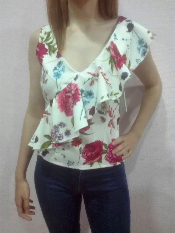 Blusa de mujer blanca de volantes y con estampado de flores.