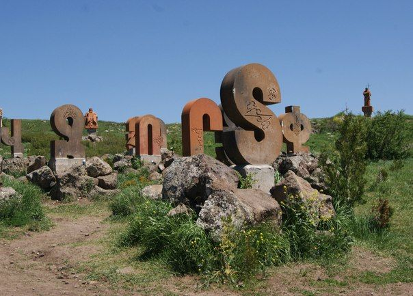 """The Monument to """"Armenian alphabet"""". The monument to """"Armenian alphabet"""" is located in Oshakan, at the east side bottom of Mt. Aragatz. The monument is erected by the design of the famous Armenian architect J. Torosyan (1962). It is an interesting demonstration of the stone carvings of 39 Armenian letters."""