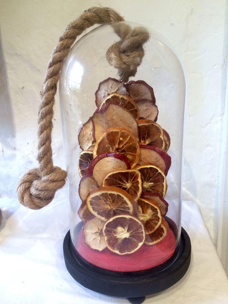 Objet de décoration globe en verre avec des pommes et oranges séchées