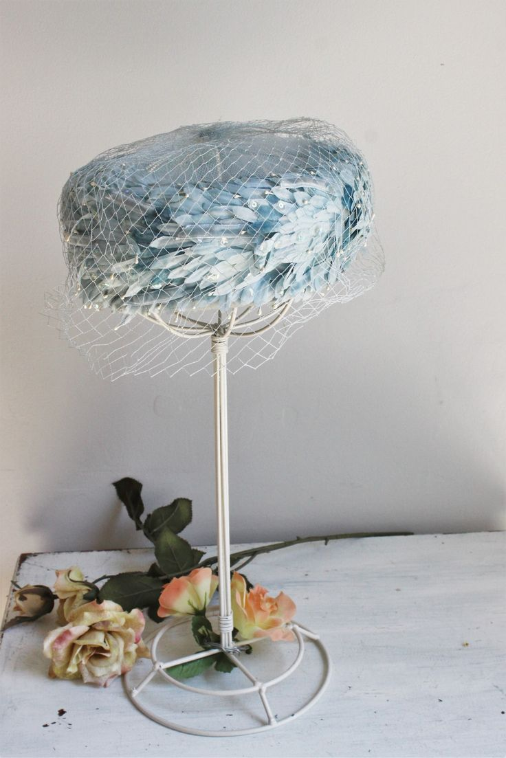 Stunning sky blue pillbox hat from the 60s with a paler blue birdcage veil. The hat is a stiff mesh covered in really neat faux feather-like pieces in velvet and silk. These are studded in various pla