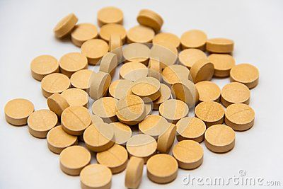 Vitamin supplement pills over gray background color. Round khaki color tablets with a line across. heap of pills. Natural mineral prescription.