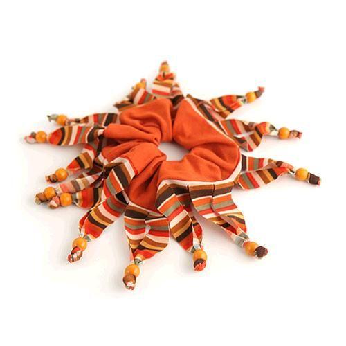 ELASTICO HEIDI ARANCIO ROSSO  -  Simpatico elastico per capelli a righine con frange decorate da pallotte in legno.