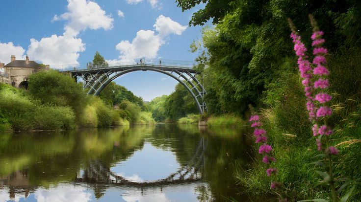 A photograph by photographer Niall O Cleirigh of the iron bridge in England with reflection and flowers and white fluffy clouds www.essentia.ie