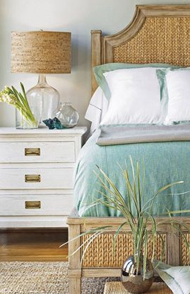 The perfect beach house bedroom! Love the rattan, natural colored wood, white/tan /sea green color scheme and the table lamp