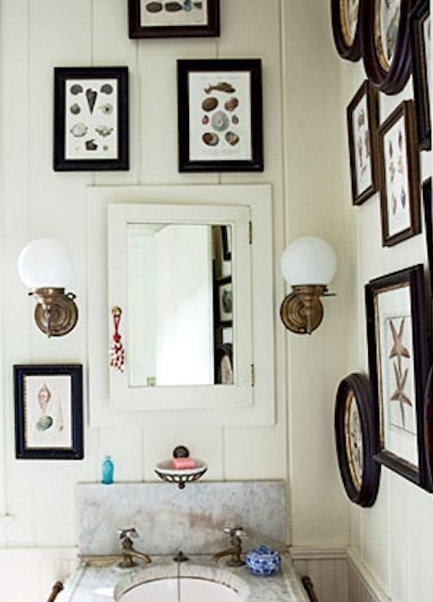 a cohesive coastal gallery wall display in a powder room
