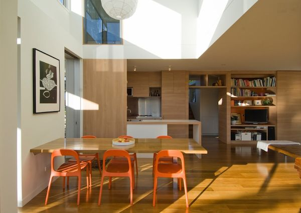 Orange and natural wood open plan kitchen living and dining area