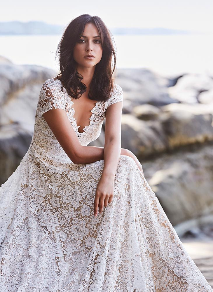 Boho lace wedding dress, guipure lace over nude lining, lace detailing on front and back V-neck lines, flared skirt extending to a subtle train. View Dress.