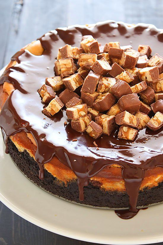 Snickers Cheesecake with Oreo crust, cheesecake filling loaded with Snickers, thick chocolate ganache, and more Snickers on top! Ultimate decadence.