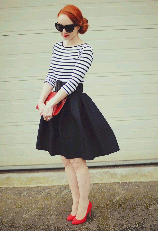 Chica usndo una falda en color azul marino y na blusa a rayas