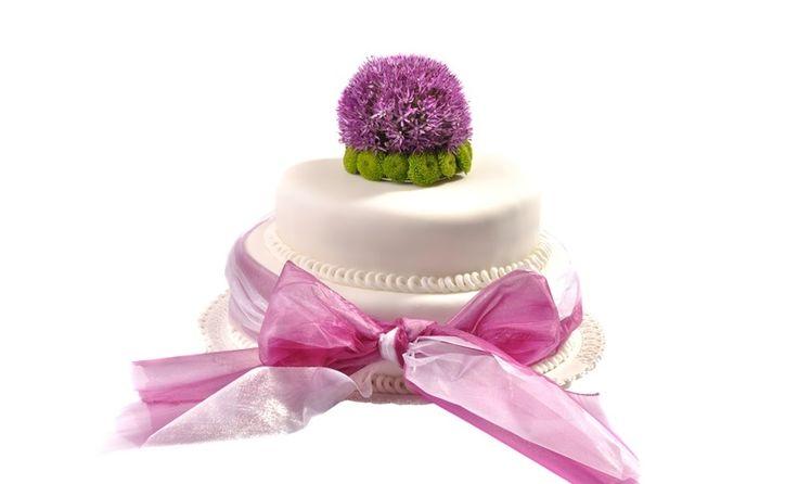 Svatební dort 43 Dvoupatrový svatební dort. o rozměrech 24 cm a 32 cm, obalen fondánem,dozdoben stuhou a kombinací živých květů