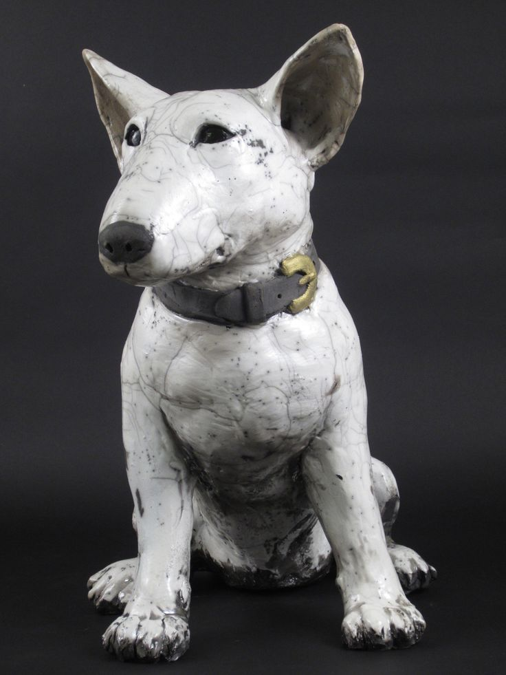 Bull Terrier by Ronnie Gould. Hand-built from stoneware with applied porcelain slip. Raku glazed in crackle white. Best for indoor enjoyment and not exposed to freezing temperatures.