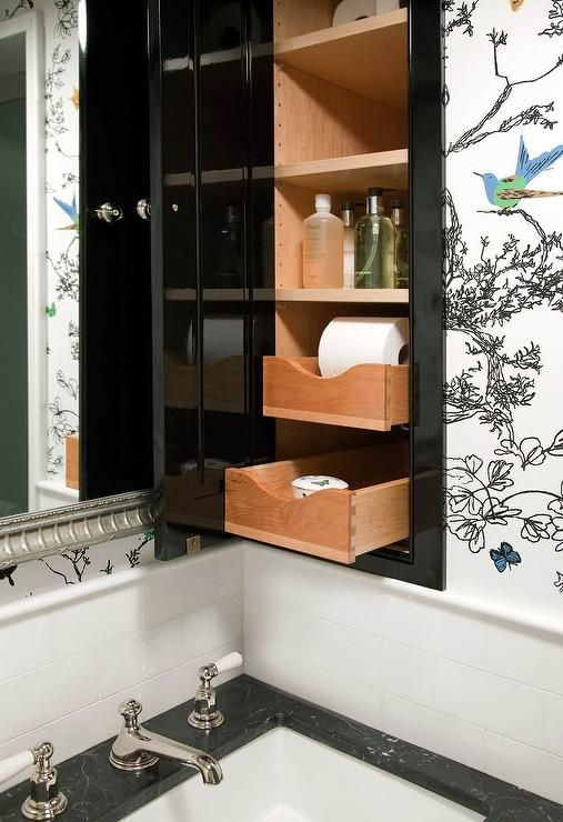 Contemporary bathroom features upper walls clad in Schumacher Birds and Butterflies Multi on White Wallpaper and lower walls clad in white subway tiles lined with a black marble top washstand and a silver mirror next to a glossy black medicine cabinet fitted with wood pull out drawers.