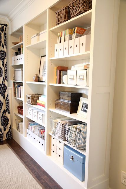 Use IKEA Billy to make a built in floor to ceiling wall to maximize vertical storage space.