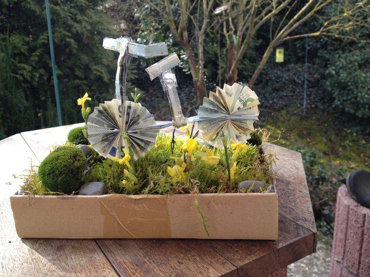 Fahrrad aus Geldscheinen gefaltet. Die Anleitung zum Falten findet ihr hier: http://www.helpster.de/geld-falten-als-fahrrad_204023 Den Karton habe ich mit Folie ausgelegt und mit Moos aus unserem Garten ausgekleidet. anschließend ein paar Zweige von gelben Jasmin abgezwickt und ins Moos gesteckt. Zum Schluss wird das Fahrrad mit einem dünnen Draht im Moos befestigt.