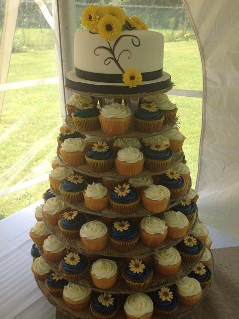 Assorted flavored cupcakes adorned with tiny sunflowers in keeping with the theme of the wedding