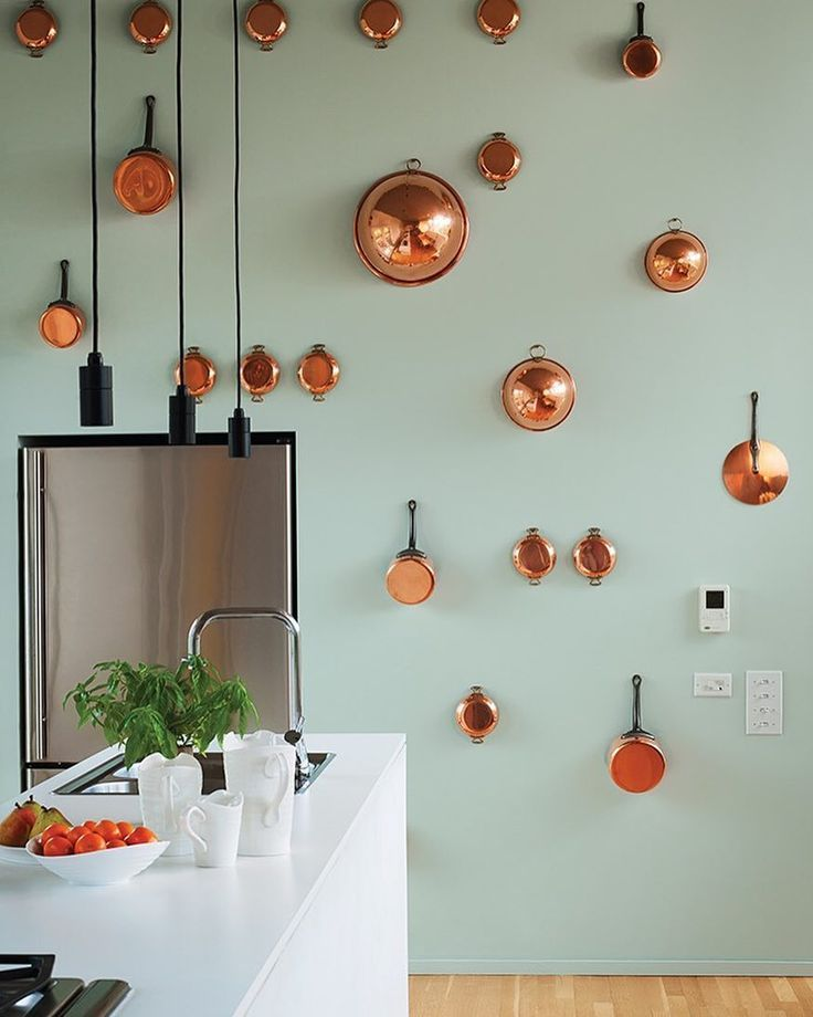 """Fun with Copper. ...""""Orrill wanted the kitchen to be command central for entertaining so everything is kept inside minimalist cabinetryexcept for the copper pots and pans hanging on the back wall painted in Pale Water by ICI Dulux Paint. The refrigerator is by Jenn-Air and the faucet is American Standard... More on http://Dwell.com  Photo: Caren Alpert / #dwell #copper #kitchen"""