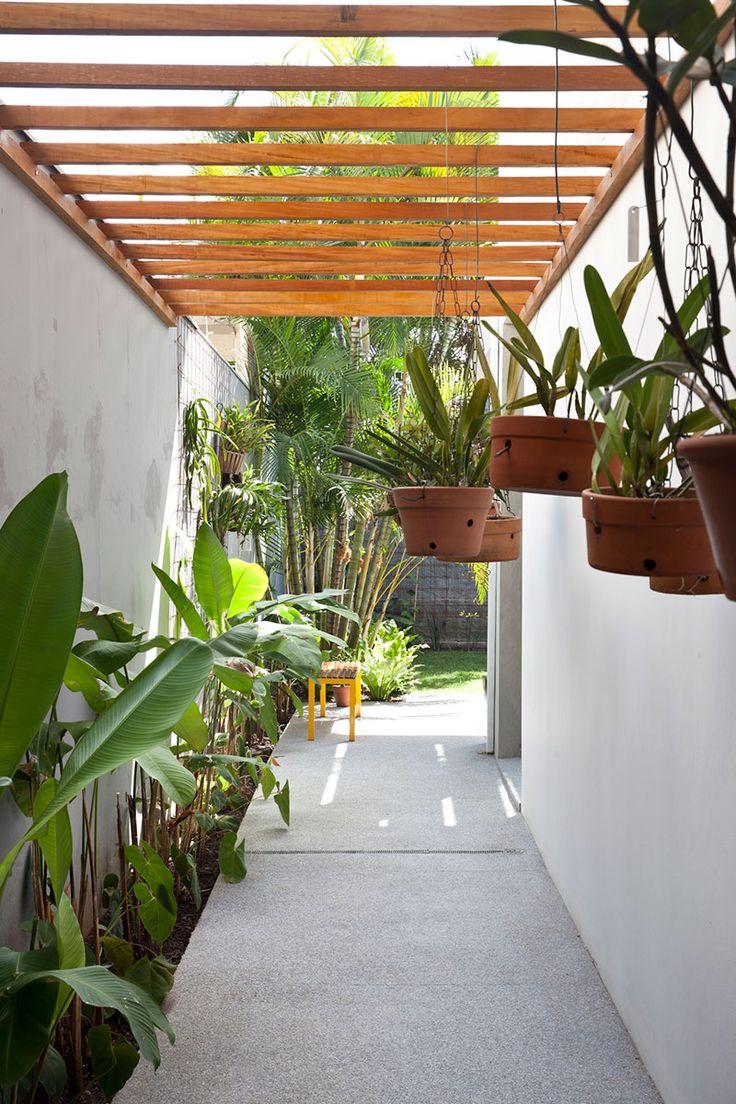 Decoração de sobrado com luz natural. No corredor, madeira, plantas e luz natural.