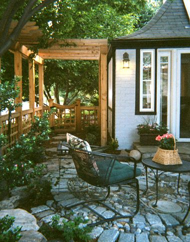 This #patio bounded by a #pergola with foliage inside and outside the pergola creates privacy from a busy street.