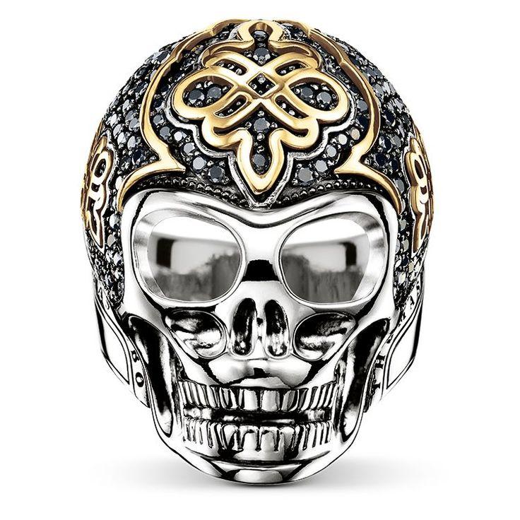 THOMAS SABO-ring från kollektionen Fine Jewellery. Den ikoniska dödskalleringen från THOMAS SABO, tillverkad av 925 sterlingsilver, som attraherar allas blickar med dess utsökta kärleksknutsdetaljer och bländande svarta pavéinfattade diamanter. [Artikeltabelle]Kategori:Ring Material:svärtat 925 sterlingsilver, 18k gult guld Stenar:svart diamant (1,01 ct) Mått:storlek ca 3,1 cm (1,21 tum) Artikelnummer:J_TR0015-723-11[/Artikeltabelle]