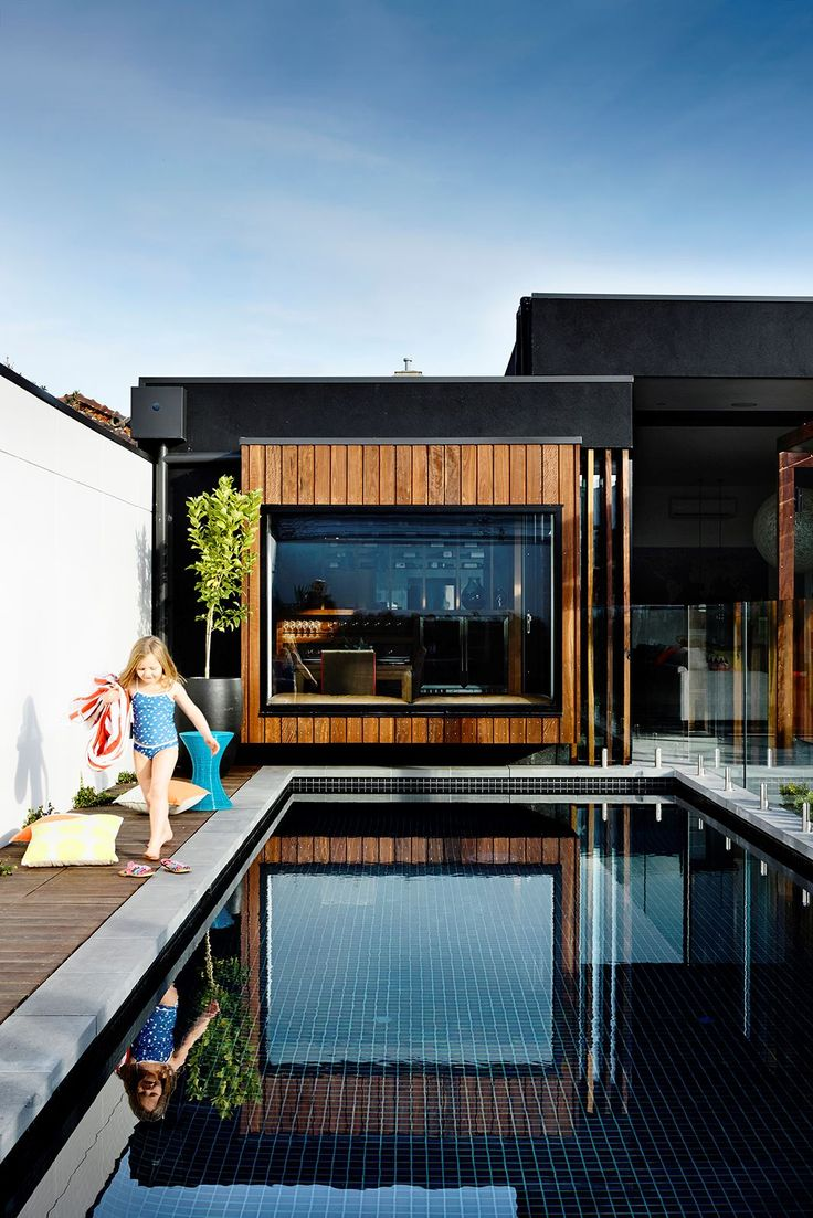 """This 9x3m pool in Melbourne was designed to be """"season-less"""", says owner Andy Mullins. """"We wanted it to be an exciting space to dine by, swim in, walk past and look at from inside with the fire going."""" A dark-tiled interior is combined with bullnose bluestone tiles and spotted gum decking. **Cost:** about $85,000. Photo: Derek Swalwell: [object Object]"""