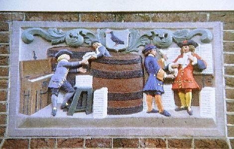 Tafereel van lakenhandel de Snep (zie het vogeltje). Laken, een zware, wollen stof, werd in tonnen vervoerd. Al rollend was de last zo minder zwaar. Gevelsteen in de Frankenstraat, Haarlem
