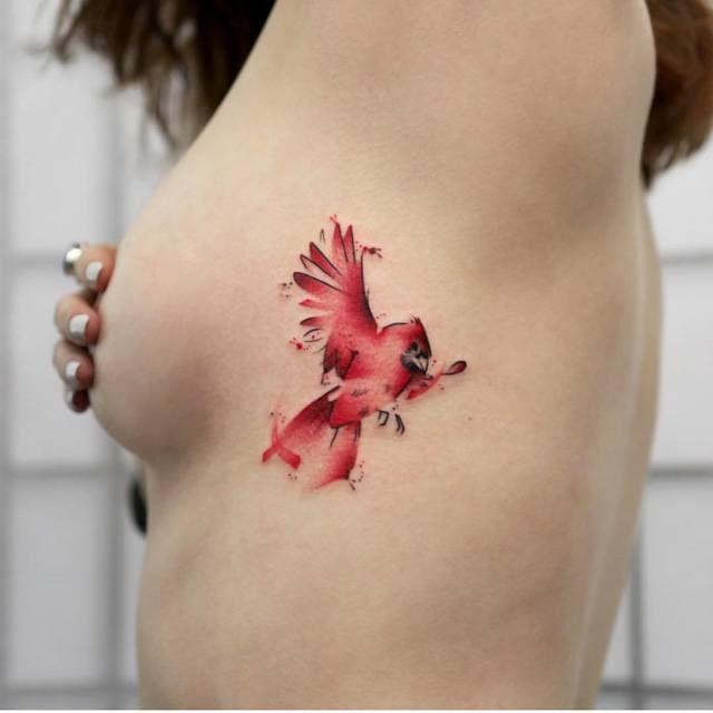 watercolor red bird tattoo on ribs