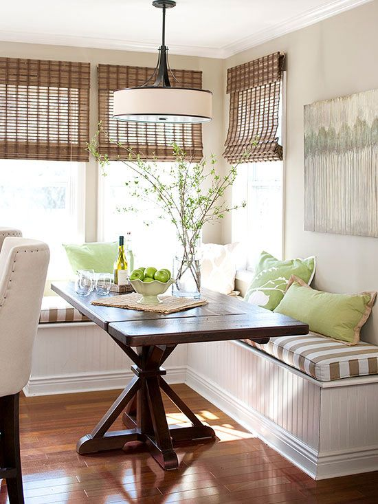 Utilize a sunny kitchen corner with L-shape banquette seating. A simple rectangular table fits snugly against the bench and provides ease of movement in and out of the dining area. Bamboo blinds, muted wall color, and earth-tone upholstery keep the space light and airy.