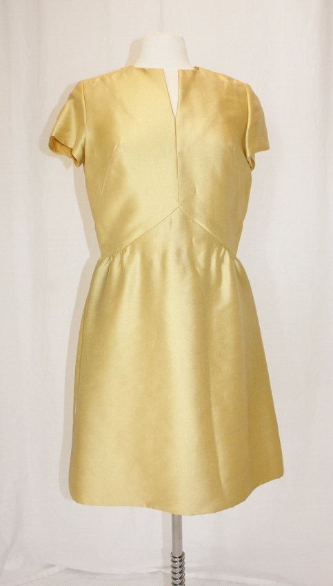 Vintage 1960s dress with a fitted bodice and gathred skirt.    Dress has short sleeves and v-slit neckline.    Long back zipper closure.    Matching