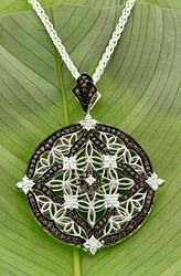 PPS0101 Keith Jack Sterling Silver Round Large Night & Day PENDANT   The fascination of the night sky – the brilliance of stars, delicate traces of the Milky Way, the infinite imaginings of space. A ring of chocolate colored zirconia surrounds a delicate silver filigree of trinity knots, and a starry compass of clear zirconia. Pendants are two sided. It reverses to the brilliance of sunlight sparkling on the water. Sterling Silver.
