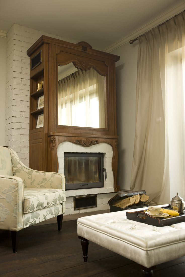 wood sculpted decorative fireplace with a mirror, wodden fireplace, quilted coffee table, floral armchair, pastel interior