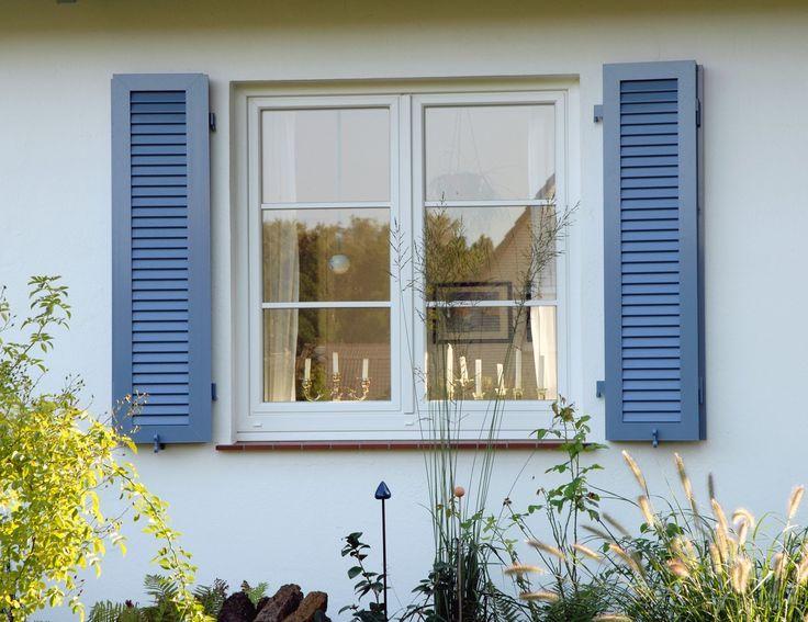 Ganz schlicht – Ein Sprossenfenster aus Kunststoff in weiß. Außen verschönert mit Fensterläden in einem Blauton
