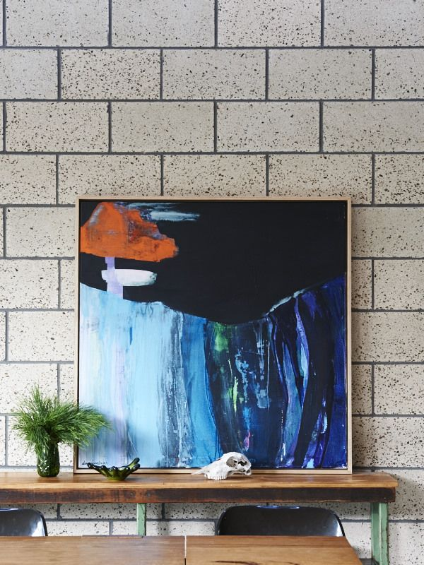 The honed block work in the dining room is a striking feature, and an excellent backdrop for this painting by Ali McNabney-Stevens. Image by TDF #archiblox #thedesignfiles #honedblock #art #alimcnabneystevens