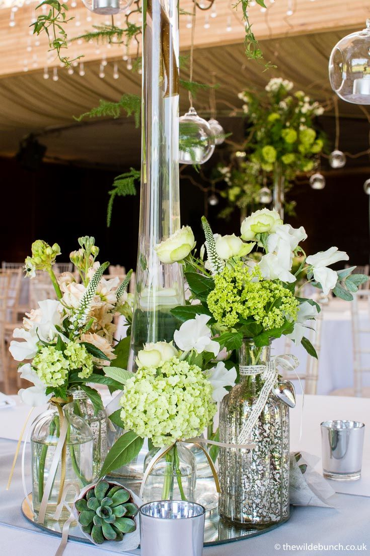 The base of a tall vase design. The little details of mercury bottles and a mirror stand give this Wilde Bunch wedding design that bit more style that set our designs apart from the rest