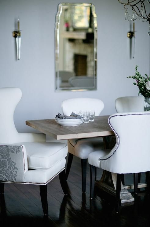 chic dining room features a wood trestle dining table lined with white nailhead dining chairs as well as white and gray embroidered dining chairs placed at