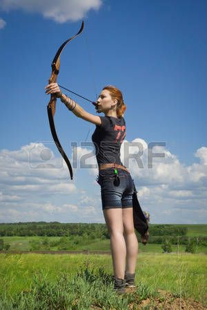 archery woman: Archery woman bends bow archer target narrow in the summer field