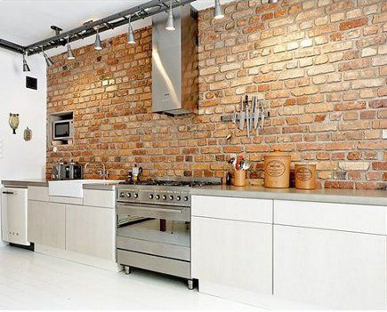 exposed natural brick wall in a Dutch loft minimalist white kitchen