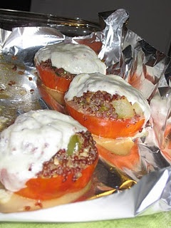 Stuffed tomatoes with quinoa, bell pepper, and onion. Topped with melted mozzarella cheese