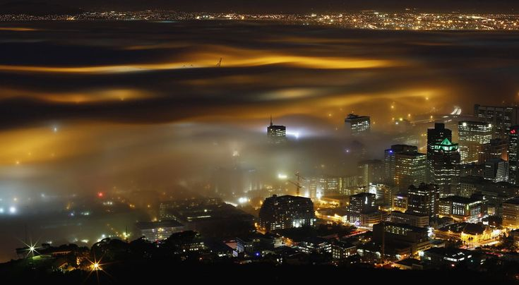 Seasonal fog is illuminated by the lights of Cape Town harbor as the city prepares for the start of winter in the southern hemisphere, on May 8, 2012. (Reuters/Mike Hutchings)