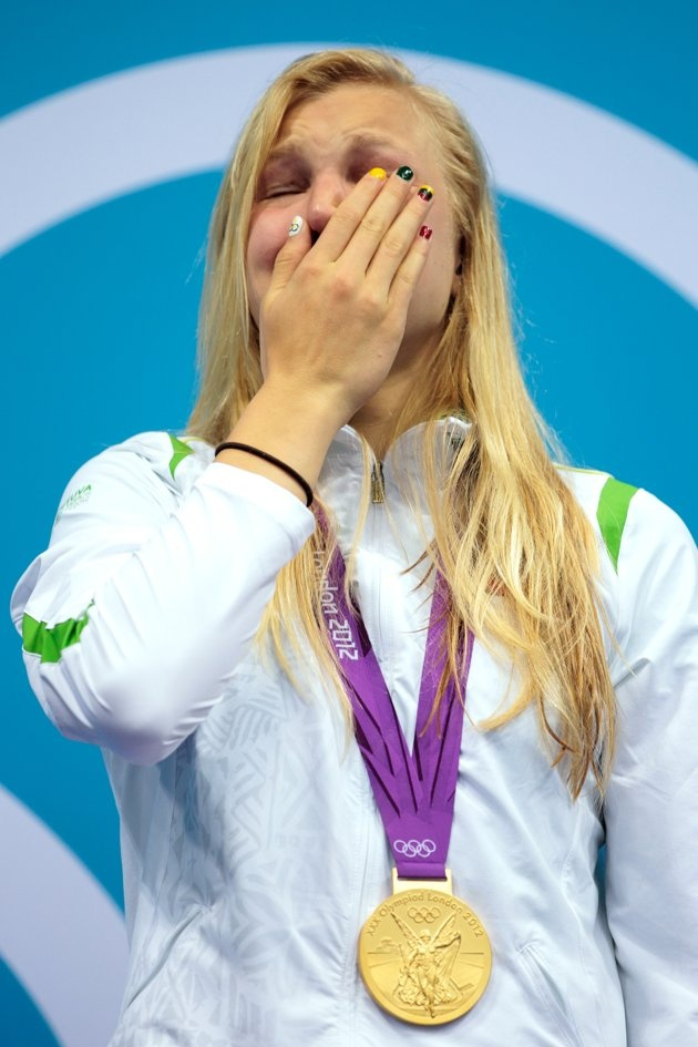 Ruta Meilutyte–Lithuania–SwimmingJ  Ruta Meilutyte of Lithuania reacts as she receives her gold medal during the medal ceremony showing off her patriotic nail varnish for the Women's 100m Breaststroke on Day 3 of the London 2012 Olympic Games at the Aquatics Centre on July 30, 2012 in London, England.