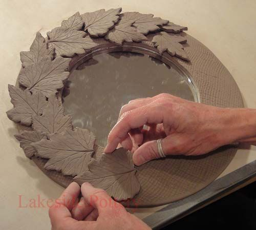 Pressed leaves on mirror frame http://www.lakesidepottery.com/Pages/Pictures/Handbuilding-projects-ideas-pictures.html