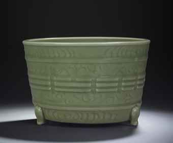 A LARGE CARVED LONGQUAN CELADON-GLAZED TRIPOD CENSER MING DYNASTY, 14TH/15TH CENTURY The censer stands on a short bi-shaped foot and has a flat base and flaring cylidrical sides. It is applied with three decorative cabriole legs, moulded and carved on the exterior with the Eight Trigrams around the exterior. It is covered with an even olive-green celadon glaze stopping around the base. 9 1/8 in diam