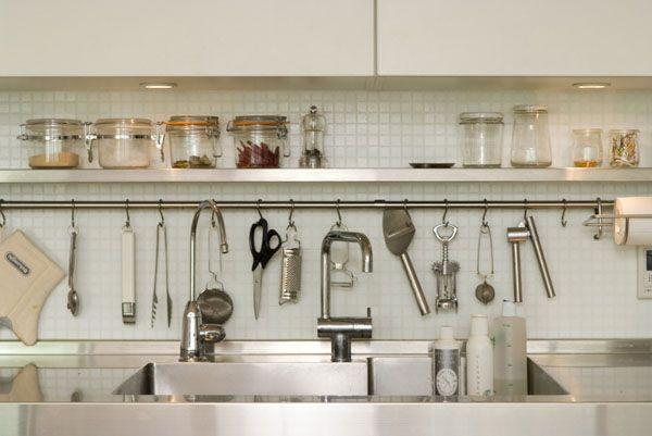 白い扉とステンレスカウンターのシンプルなI型キッチン。 レンジフードのデザインに...