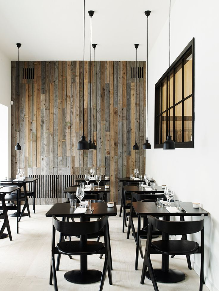 Design Inspiration | Restaurant Radio, Copenhagen. A considered, understated and sophisticated interior. Black furniture and industrial pendant lighting look striking against the recycled timber wall panelling and wide timber floor boards. #RecycledTimber #InteriorDesign