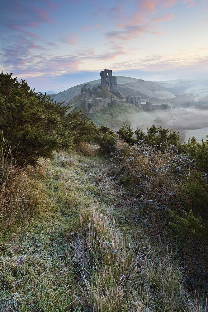 castlesfromallovertheworld:  Corfe Castle, England  The dramatic ruins of Corfe Castle stand on a natural hill guarding the principal route through the Purbeck Hills.  © Antony Spencer