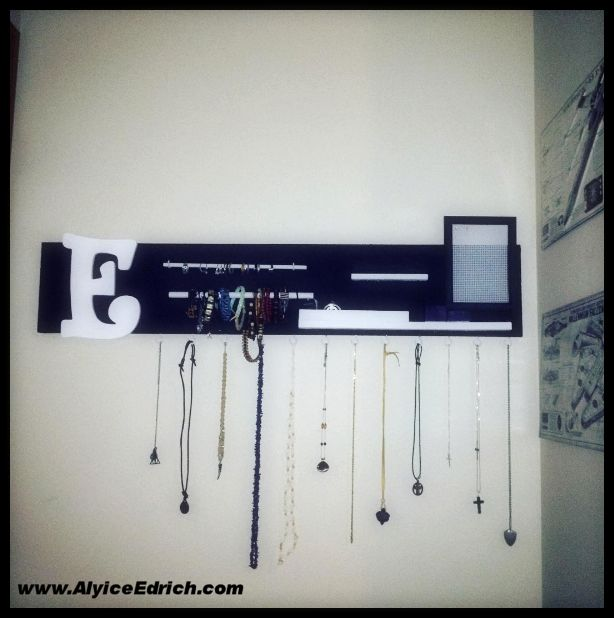 Alyice Edrich - circa 2016 - Wood Jewelry Organizer - My daughter has a black and white room theme. She likes simple, non-frilly things and we needed something to display her costume jewelry... It's made out of scrap wood, black paint, white paint, wood dowels, black frame, plastic mesh, wood letter, coffee cup hooks. #costumejewelry #jewelryorganizer #jewelrybox #jewelryhangers #wood #wallhanger
